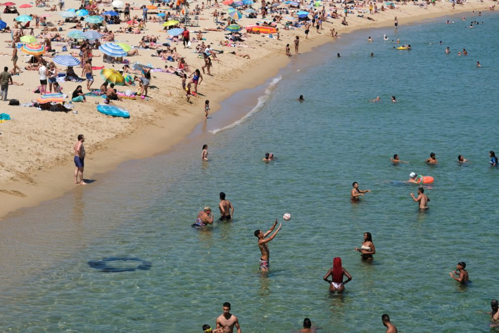 Catalonia urges 4 MILLION people to stay at home over coronavirus spike fears but beaches still packed in 30C sun
