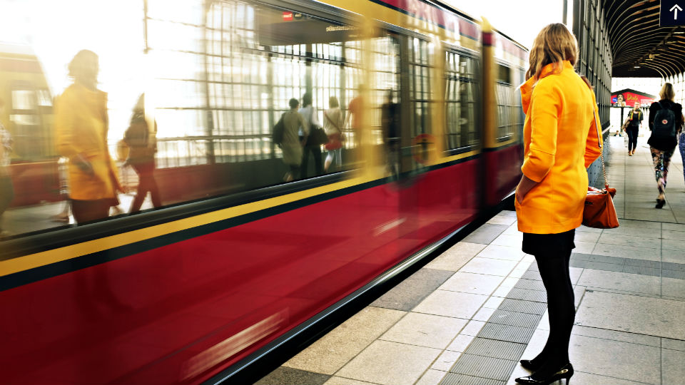 Woman in yellow coat next to train
