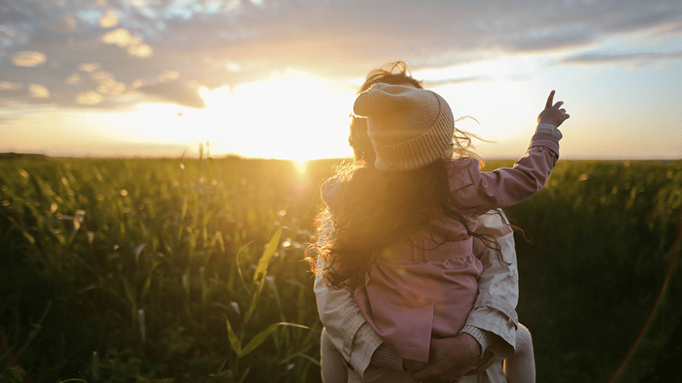 Parent and child in a field watching the sunset