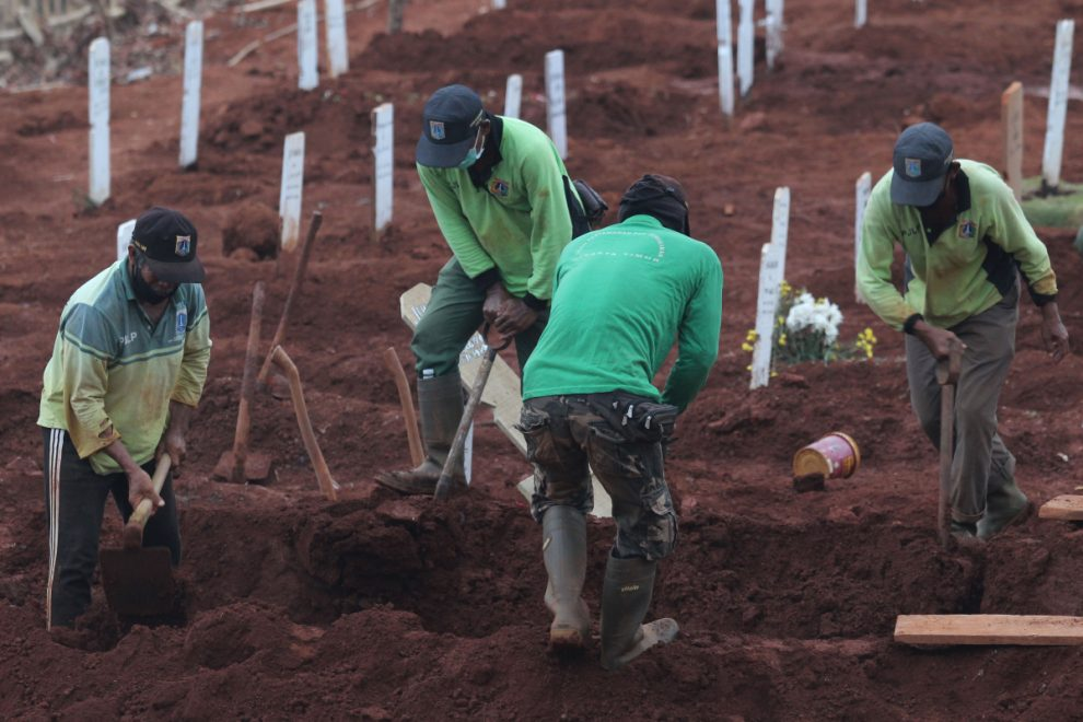 Covidiots caught not wearing face masks forced to DIG GRAVES for coronavirus victims in Indonesia
