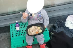 Fury as homeless girl, 4, spotted eating 'only hot meal of day' out of plastic container on the street